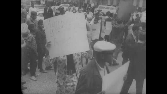 1960s: Men marching with signs. Muhammad Ali talking to press. View of crowd, demonstrators. Ali talking to press. Intertitle. Man on platform waves flag, pan of racecars passing.