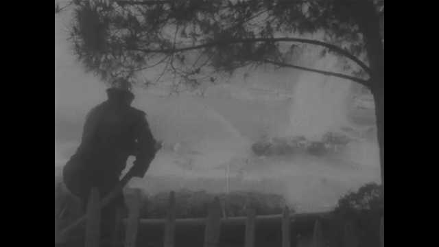 1960s: Man aims hose towards car on fire. Men remove body from car.