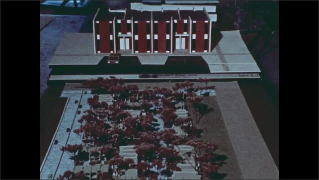 1970s: Scale model of building project. Man sits in office, talks. Men walk down steps, talk.