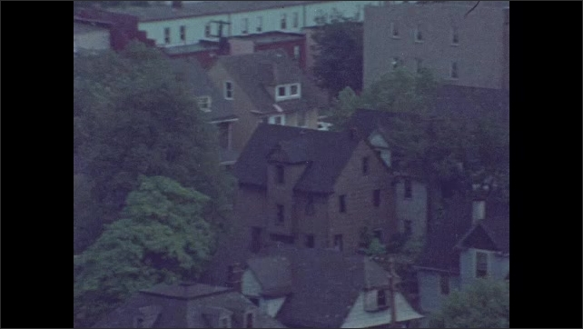 1970s: Neglected inner city street with shops. Houses, trees, buildings.