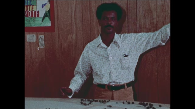1970s: Man stands in front of display table, talks.