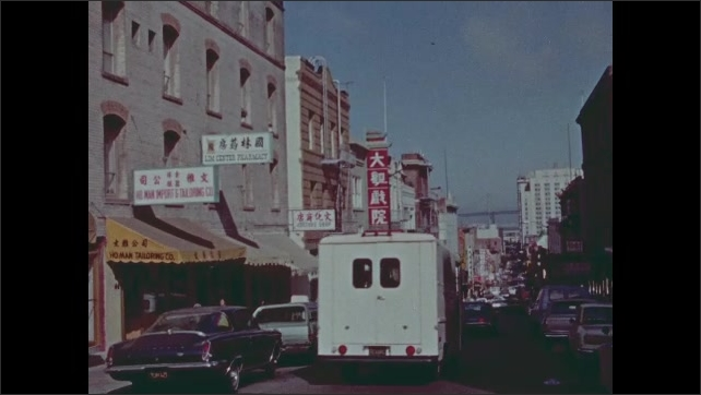 1970s: City of San Francisco and Golden Gate Bridge. Bay Bridge and Chinatown. Woman stands outside, talks. Chinese characters. Chinese signage on buildings.