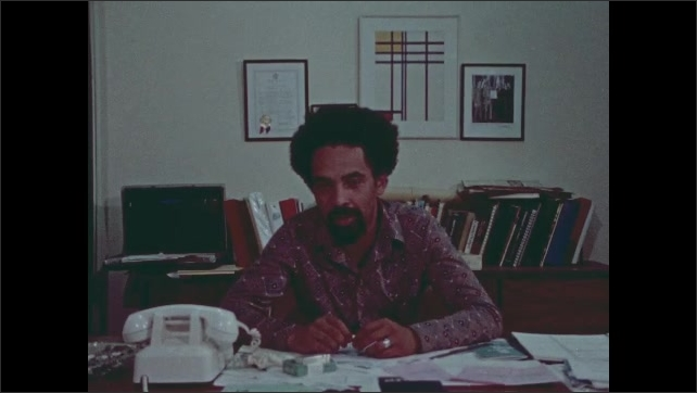 1970s: Man sits at desk, talks. Woman stands outside, talks.