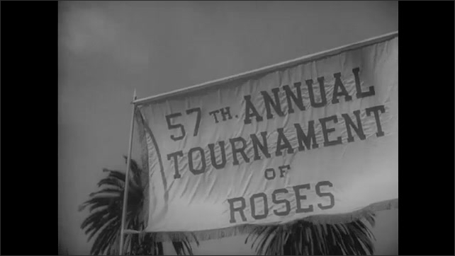 """1940s: Caption reads """"HAIL VICTORY IN CALIFORNIA ROSE FESTIVAL.""""  Men carry banner.  Parade.  War hero rides on float and waves.  Spectators line street."""