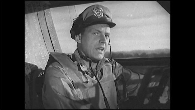 1940s: Officer loosens and removes tie. Officer sits in cockpit and speaks. Pilot straps on seat belts.