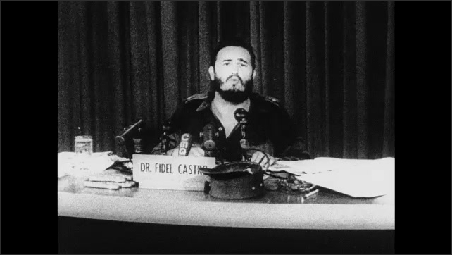 1960s Cuba: Manuel Urrutia Lleó gives speech on television. Audience in television studio. Fidel Castro sits at desk, talks. Manuel Urrutia Lleó stands talks to people.