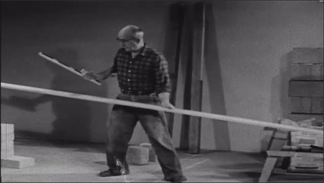 1950s: Man stands in empty room with construction supplies, points at lines on floor where walls go, while talking. Man holds long board of wood, talks.