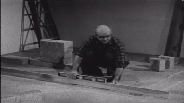1950s: Man in empty room with construction supplies, talks, places level on wood plank on floor. Man adjusts wood plank. Man grabs large block, moves plank, puts block in its place.