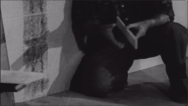 1950s: Man points at grooves on brick wall, while talking. Man knelt on floor in room, places concrete block on floor, against wall, then a block next to it.
