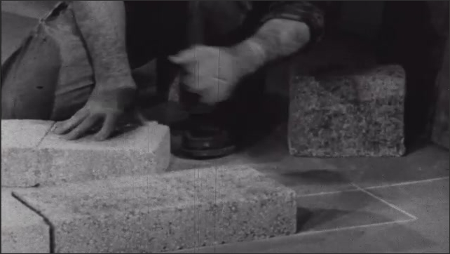 1950s: Man knelt on floor in room with concrete blocks in row making base of wall. Man motions at blocks on floor while talking.