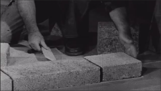 1950s: Man knelt on floor in room places concrete block in row of other blocks, along floor, creating base of wall. Man marks measurements on wall.