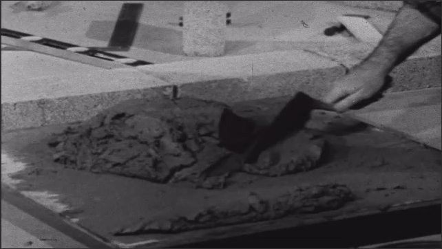 1950s: Man knelt on floor in front of mortar on plate, sorts mortar with tool, into lines then pushes them all together.