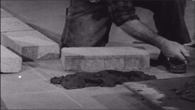 1950s: Man knelt on floor in room spreads mortar on floor then places concrete block on top of that and presses it down.
