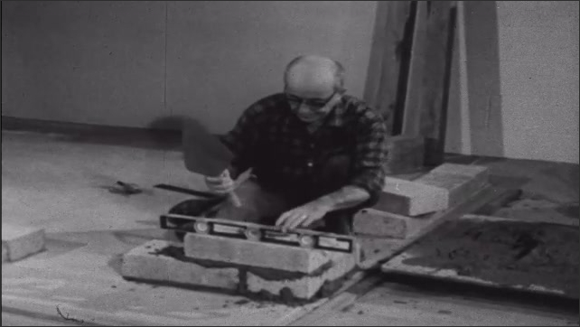 1950s: Man knelt on floor in room uses level to square off concrete blocks and mortar, building a wall.
