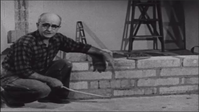 1950s: Man talks while laying concrete blocks on top of other concrete block making wall, man points to gaps in wall. Man talks next to blocks forming a wall.