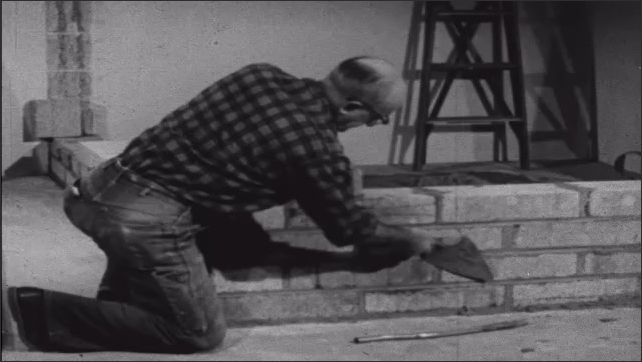 1950s: Man knelt on floor uses stick to clean edges of concrete blocks and mortar forming to make wall. Man stands in room talking, pointing at lumber leaning against wall.