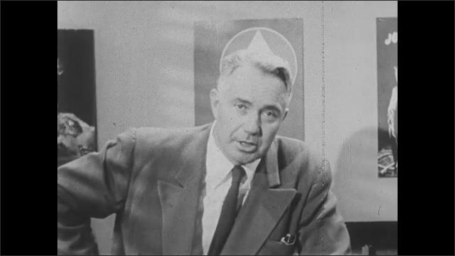 1950s: Man leans on desk, talks, looks serious, raises eyebrows, puts hand on hip, picks up paper.