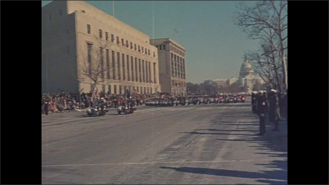 1960s Washington DC: US Capitol Building, soldiers cross wide empty street. Formation of vehicles, flags. Crowd watches parade, women sit on bleachers, wave flags, smile, cheer, wear hats, coats.
