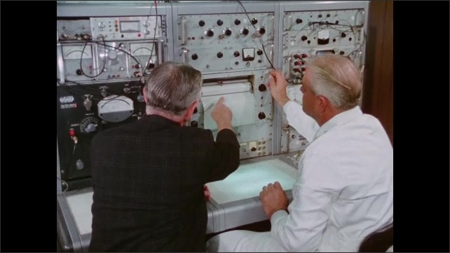 1970s: Equipment prints out graph. Men look at graph.