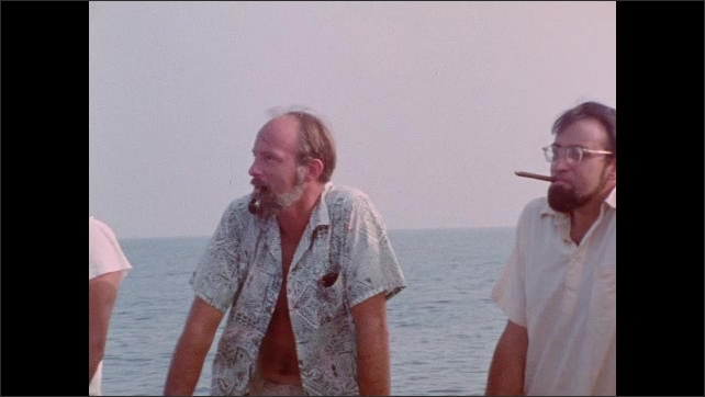 1970s: Ships sits in ocean. Men stand on boat. Man smokes cigar, laughs.