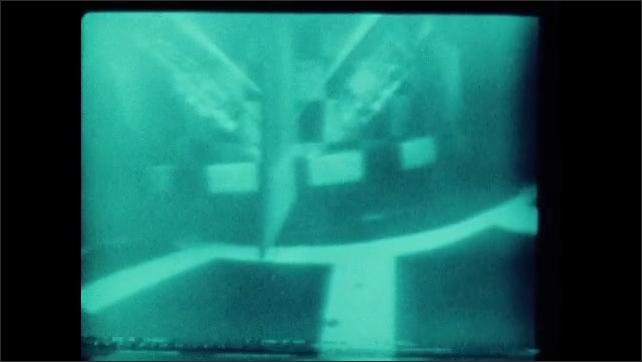 1970s: smaller submarine docking onto the larger submarine underwater