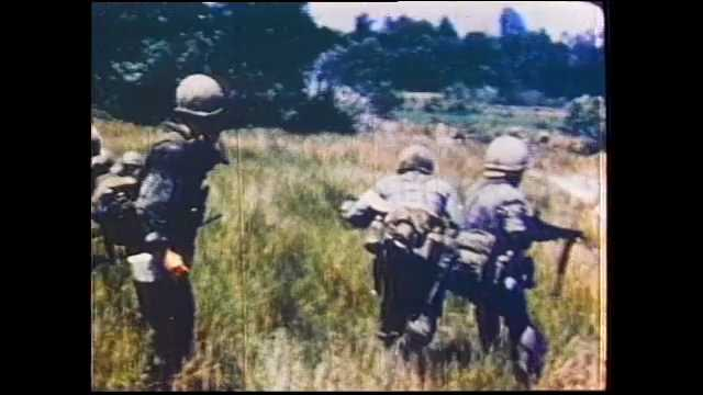 1970s Vietnam: Soldiers run through field. Men load artillery cannons, Planes bomb jungle. Medic wipes blood from wounded soldier's arm.