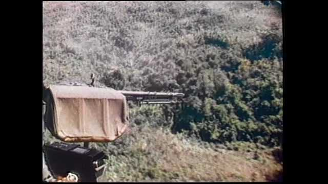1970s Vietnam: Soldiers deploy from helicopters onto fields. Soldiers carry wounded to evac helicopter. Soldiers unload supplies from helicopter. Soldiers fire howitzer cannons.