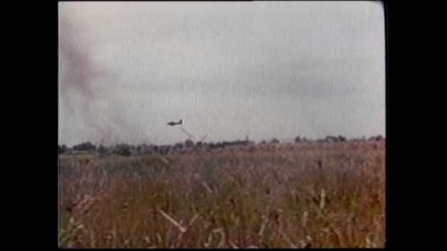 1970s Vietnam: Plane drops bombs in field. Soldiers inspect Vietcong bunkers and trenches in jungle. Soldiers walk on airstrip near helicopters.