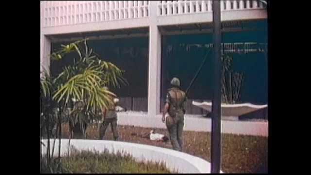 1970s Vietnam: Vietcong attack U.S. Embassy in Saigon. Soldiers exchange gunfire in streets of Saigon. Tanks roll across field.