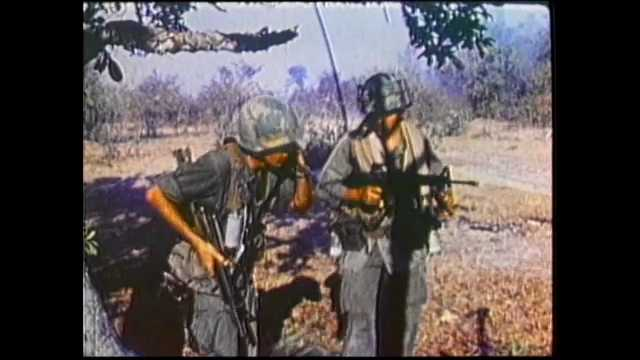 1970s Vietnam: Soldiers fire artillery and bombard jungle. Soldiers stand near cache of weapons on ground. Bulldozers clear trees and brush from jungle.