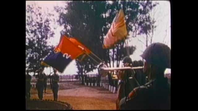 1970s Vietnam: Soldiers stand at attention during ceremony. Men fold United States flag. Soldiers depart bases in Vietnam. Soldiers carry flags and march in ceremony before audience.