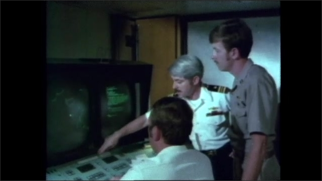 1980s: Woman marks on geographical map on table. Three men talk while looking at radar image on computer monitor.