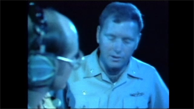 1980s: Two officers on navy vessel talk, look at map. Person adjusts measuring device on deck of ship at sea.
