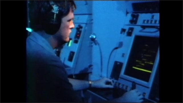 1980s: People at computers in room. Navy ship at sea. Helicopter over sea. Pilot operates radar controls. People in front of radar screens. Radar screen. Man talks into headset. Ship navigations.