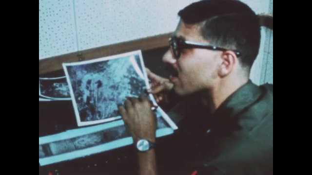 1960s: Men study photos and speak. Man looks at film through loupe. Men at work in photo lab.