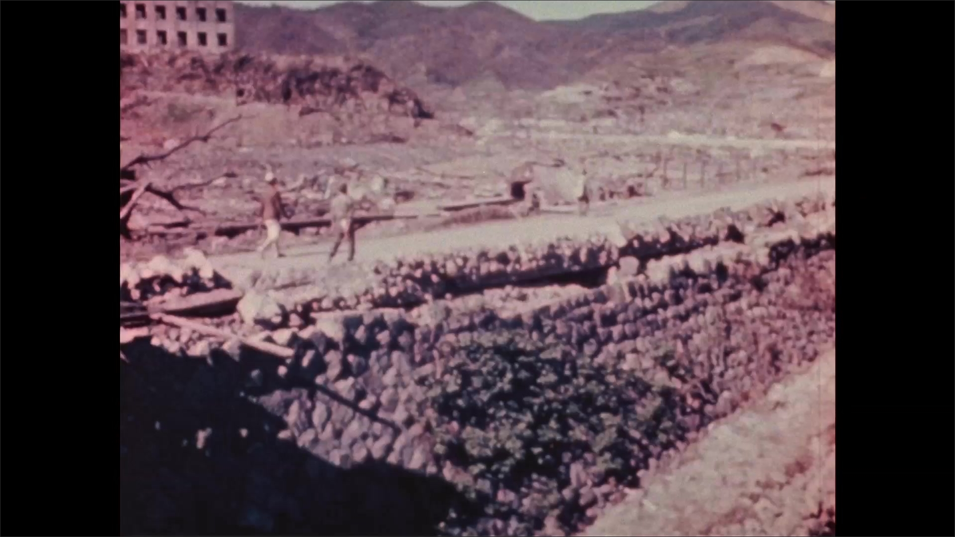 1940s Nagasaki: Mountains, rubble, dirt, partially collapsed building, windows blown out. People walk down road. Horse pulls cart.