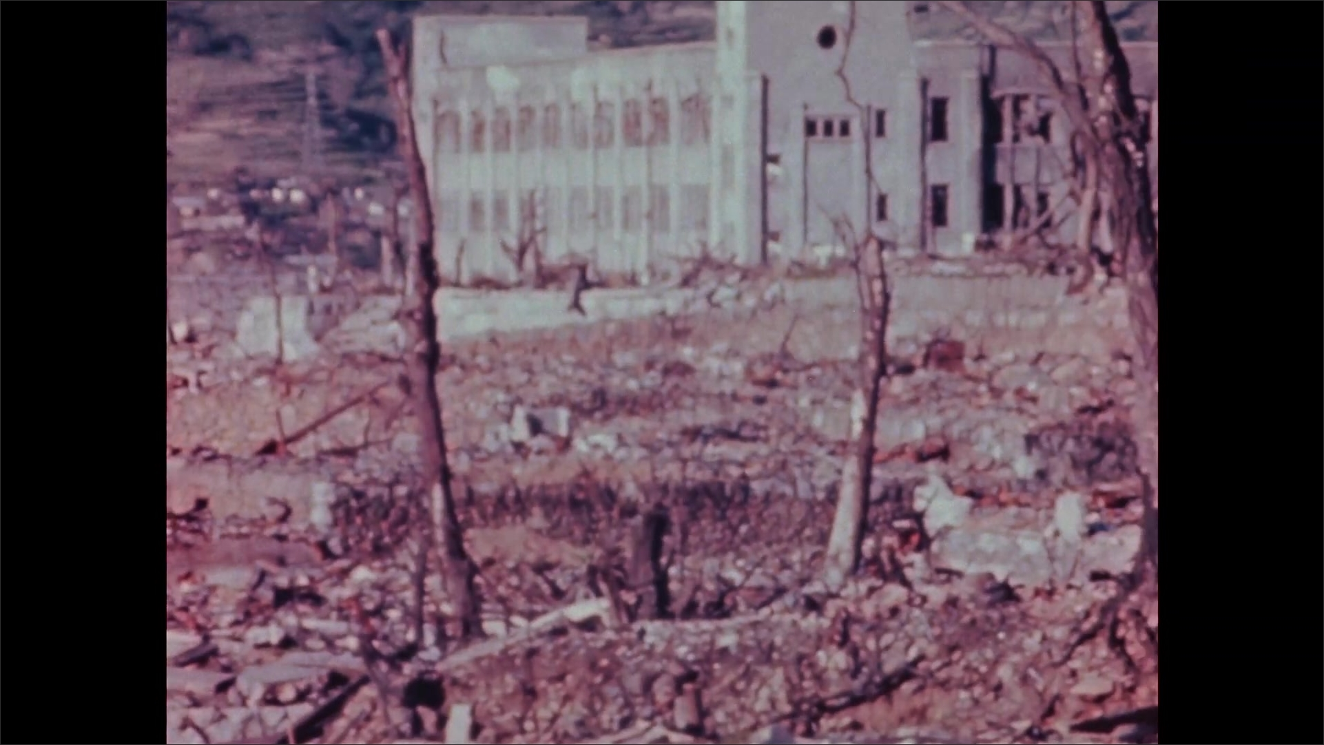1940s Nagasaki: Mountains, terraced hillside, dirt, rubble, broken trees. Remains of buildings, windows blown out. Chimney, concrete slabs, person squats, stands.