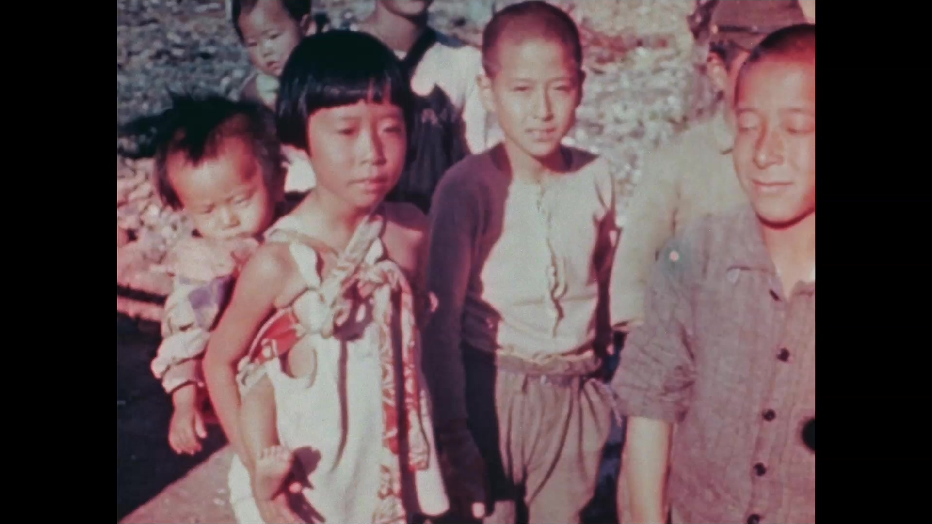 1940s Nagasaki: Rubble, children. Woman, girl wear babies strapped to backs in cloth sling. Woman holds out hand, receives object, smiles, laughs, raises hand, looks skeptical, turns, leaves.
