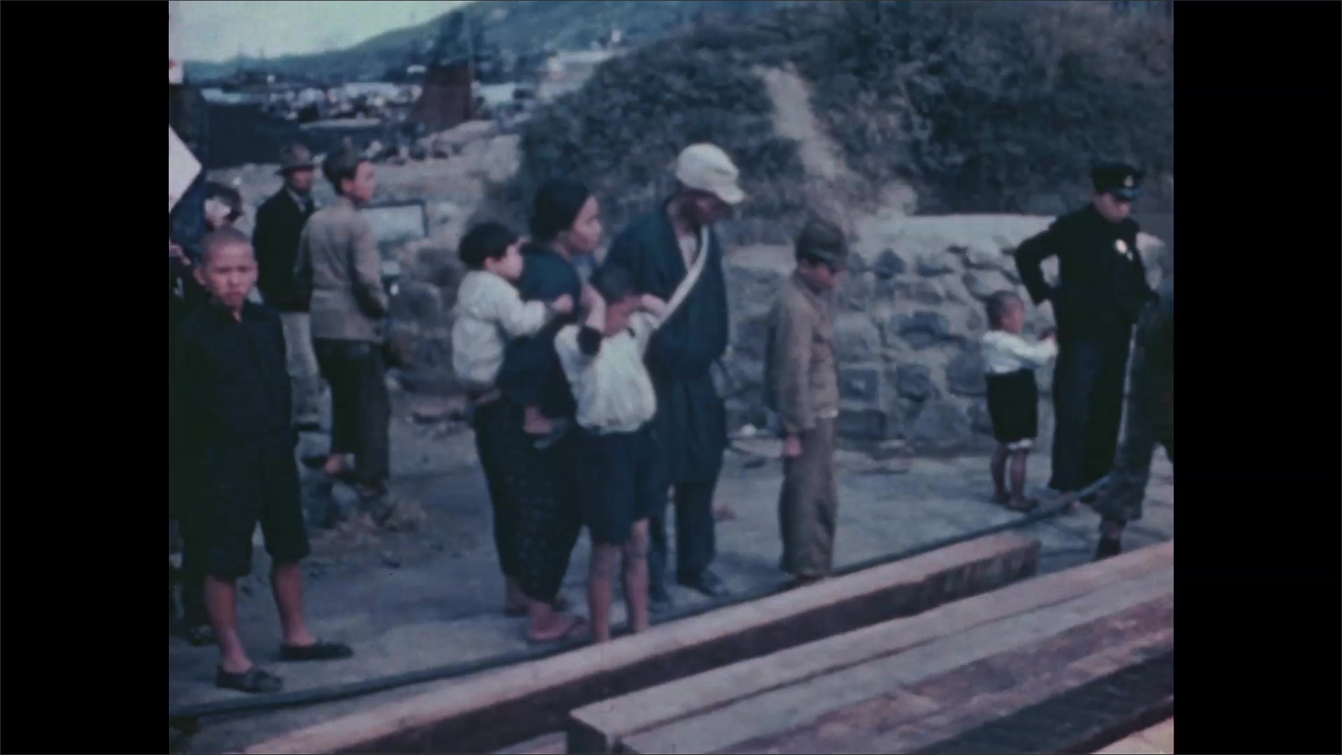 1940s Nagasaki: Neighborhood, soldiers hold steel clamp on wooden beams, children, families, police officers watch. Water, partially built bridge, soldier bangs mallet.