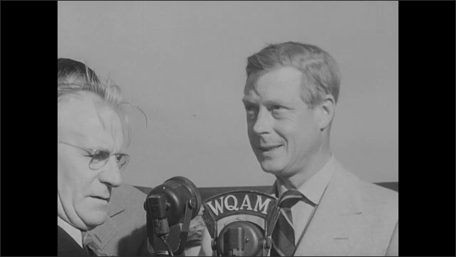 """1940s: Men talk and watch airplane take off.  Graphic reads """"UNIVERSAL NEWSREEL.  MIAMI, FLA.""""  Duke of Windsor walks into crowded stadium and speaks.  Planes perform stunts in air show."""