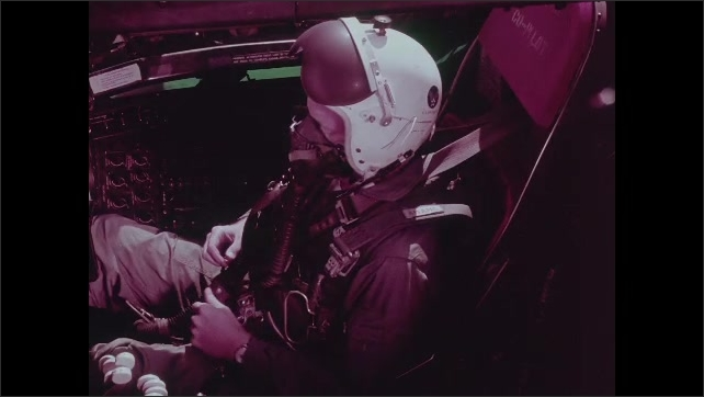 1960s: Man in cockpit puts on gas mask and adjusts harness.