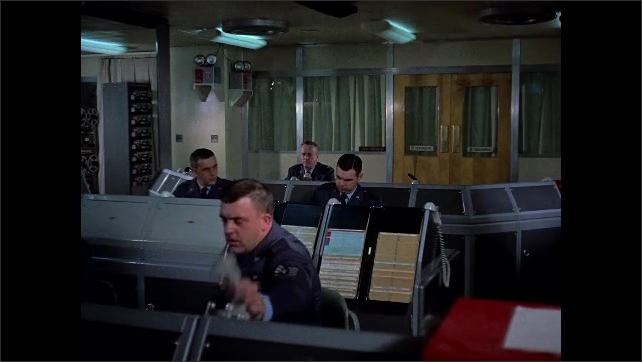1960s: film slate clapper board. Uniformed men sit at computer mainframe data terminals, speak on telephone handsets.