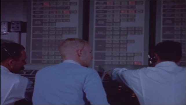 1960s: Dimly lit control room with men in white military coveralls at control boards.