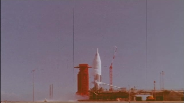 1960s: ICBM Missile is vertical on launch pad as smoke and emissions surround it.