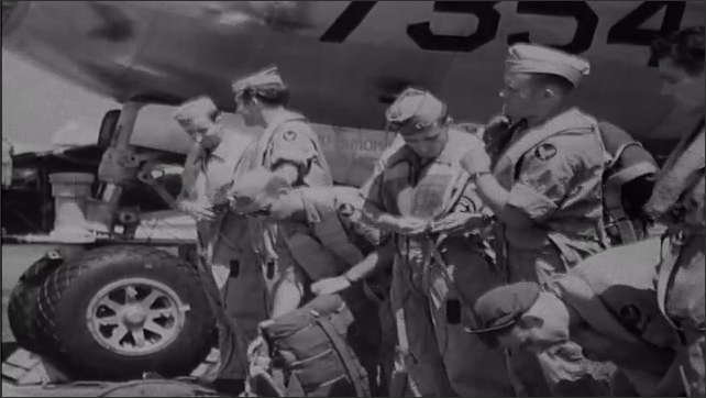 1940s Bikini Atoll: Soldiers stand next to plabe, put on parachutes and other gear.