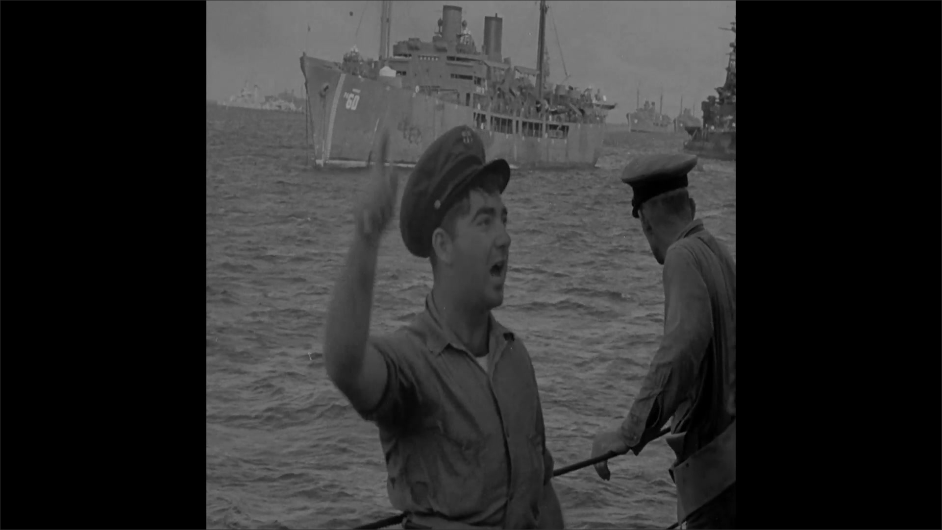 1940s: U.S. flag is raised on Navy ship. Sailors stand in salute. Officer talks to sailors, motioning above them.