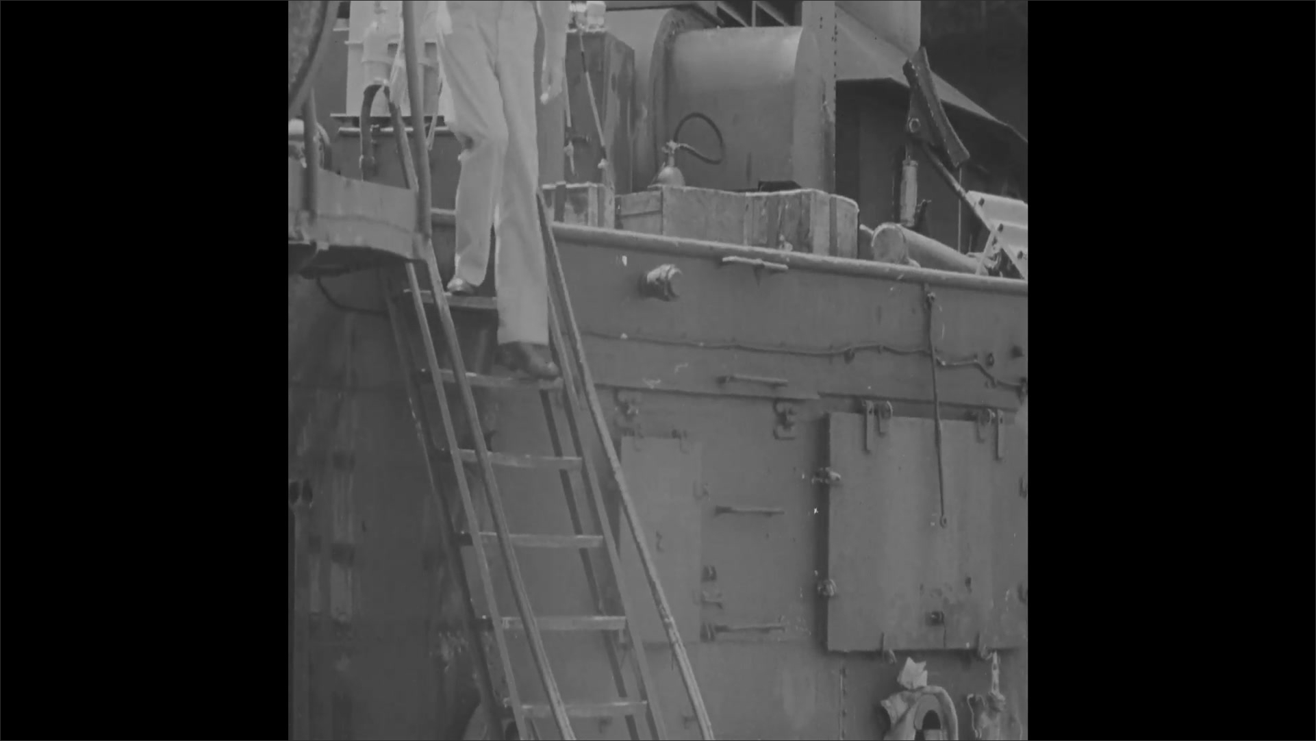 1940s: Sailors walk across deck of ship carrying duffle bags. Officer walks down steps and across deck.