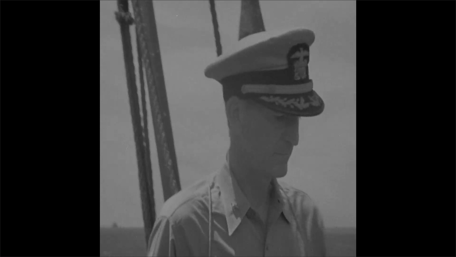 1940s: Officer stands on deck looking at ship, salutes then walks down steps to debark ship.