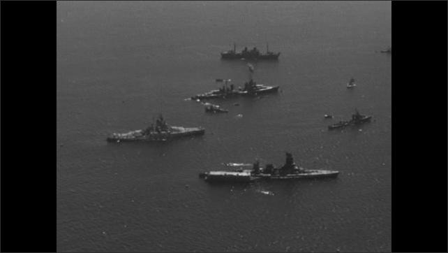 1940s Bikini Atoll: Large ships and small boats in ocean.