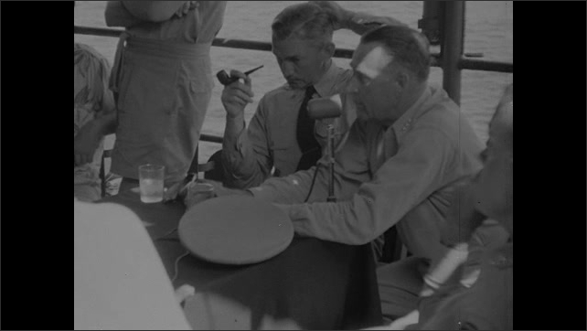 1940s: Man pours water into glasses for officers at table on deck of ship at sea. Officer at table talks into microphone. Reporters in seats talk to each other. Officer talks into mic.